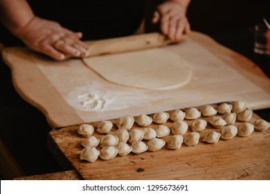 Russian pelmeni on cutting board and ingredients for homemade. Process of making pelmeni, ravioli or dumplings with meat