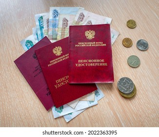 Russian pension certificates are stacked on top of each other. Paper and metal rubles are under documents and next to them. - Shutterstock ID 2022363395