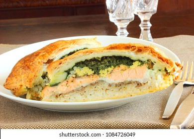Russian pie filled with egg, rice, salmon, parsley, mushrooms covered in a puff pastry