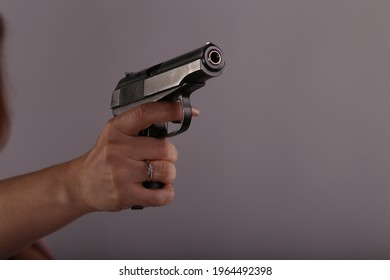 Russian pistol in female hand on grey background