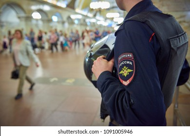 Russian police man in bulletproof vest at metro railway station Komsomolskaya with people in the background. Police is securing people and subway property. Uniform chevron text: POLICE, RUSSIA, MVD