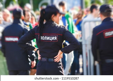 """Russian police squad formation back view with """"Police"""" emblem on uniform maintain public order after football game with football fans crowd in the background"""