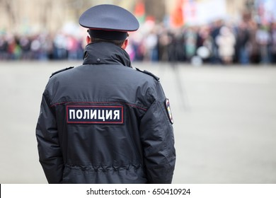 Russian policeman officer stands to opposite crowd with inscription Police on the uniform jacket, Russia, copy space
