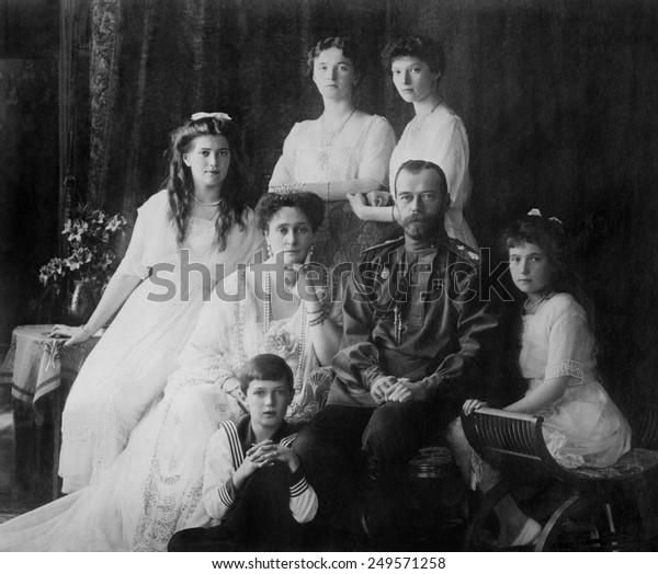 Ruská královská rodina v roce 1914. L-R Seated: Marie, královna Alexandra, cara Mikuláše II., Anastasia, Alexej. Stojící: Olga a Tatiana.