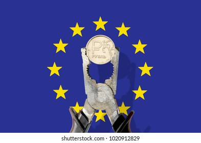 Russian ruble coin being squeezed in vice on the European Union (EU) flag background. Sanctions russia