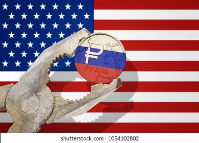 Russian ruble coin being squeezed in vice on the United States (USA) flag background. Concept anti Russian new sanctions