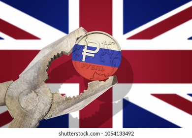 Russian ruble coin being squeezed in vice on the United Kingdom (UK) flag background. Concept anti Russian new sanctions
