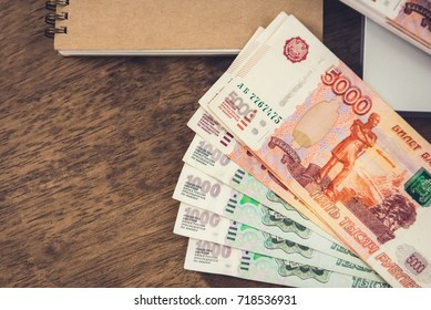 Russian Ruble (RUB )money banknotes on a wooden desk with a notebook - financial, loan and investment concepts