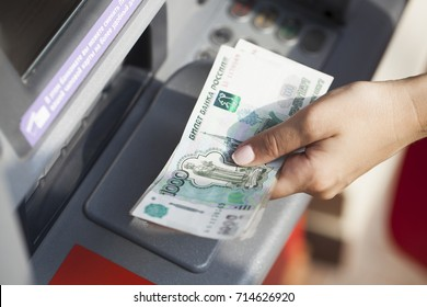 Russian rubles cash. Repayment on credit. Woman hand withdrawing money from outdoor bank ATM