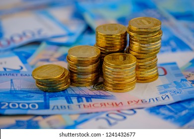 Russian rubles in coins on banknotes background.