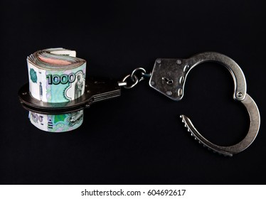 Russian Rubles and Opened Handcuffs on the Black Background