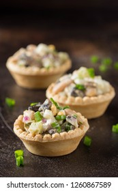 Russian salad with meat in a tartlet. With potatoes, egg, cucumber, onion, mushrooms and mayonnaise. Delicious appetizer for wine buffet