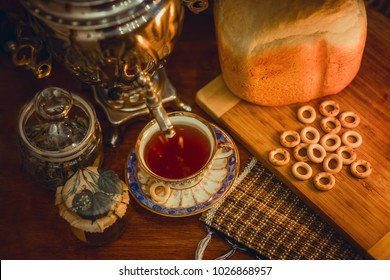 Russian samovar with hot bread and ceramic cup of tea