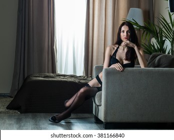Russian skinny girl in a corset and black stockings on a chair against a background of bed