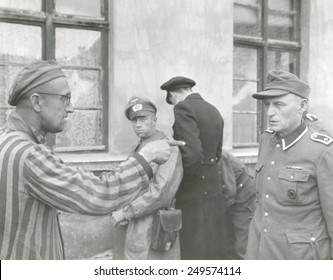 Russian slave laborer points out Nazi guard who brutally beat prisoners. The U.S. Army 3rd Armored Division liberated Buchenwald concentration Camp. April 14, 1945, Germany, World War 2.