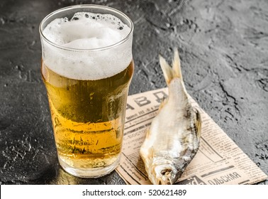 Russian snack . Beer with dried fish on black background