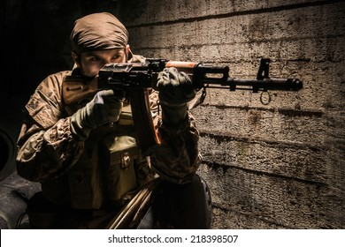 Russian soldier with kalashnikov assault rifle defending his position at night in city