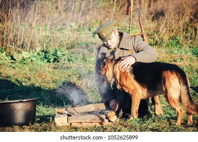 Russian soldiers of the first world war, with a rifle Mosin, shineli and worn-out cap sitting by the fire with a dog.
