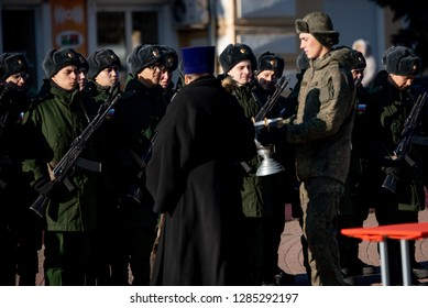 Russian soldiers recruits stand in a row with Kalashnikov rifles for the oath on square on november 18, 2018 on Boguchar, Russia. The priest blesses servicemen.