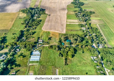 Russian sparsely populated village. Green meadows and dense shrubs. View from above.