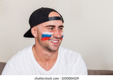 Russian sports fan with face paint laughing, indoors