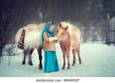 Russian style. Beautiful little girl in blue pavloposad shawl is stroking two ponies in winter in Russia. Image with selective focus and toning