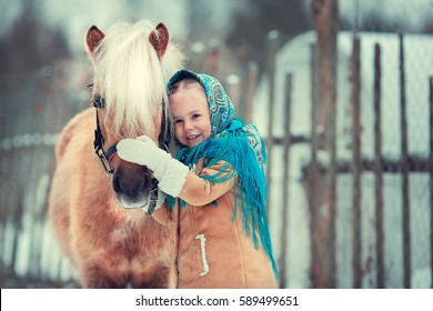 Russian style. Beautiful little girl in blue pavloposad shawl with a pony in winter in Russia. Image with selective focus and toning