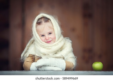 Russian style. Beautiful little girl in Orenburg shawl with an apple in winter in Russia. Image with selective focus and toning