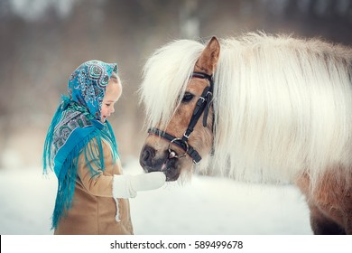 Russian style. Beautiful little girl in blue pavloposad shawl is feeding pony in winter in Russia. Image with selective focus and toning