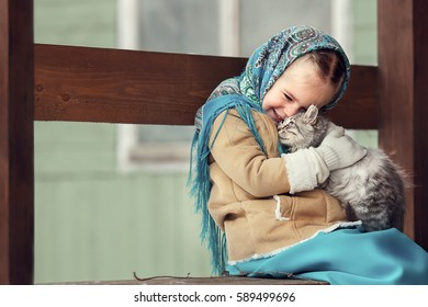 Russian style. Beautiful little girl in blue pavloposad shawl is stroking a kitten in winter in Russia. Image with selective focus and toning