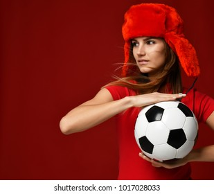 Russian style fan sport woman player in red uniform and ear-flap hat hold soccer ball celebrating happy smiling looking at the corner on red background