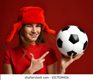 Russian style fan sport woman player in red uniform and ear-flap hat pointing finger at soccer ball celebrating happy smiling winking on red background