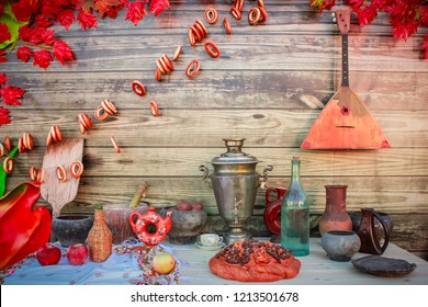 Russian style - a table with Russian dishes, a pie, a samovar, a balalaika and bagels hanging on a wooden wall
