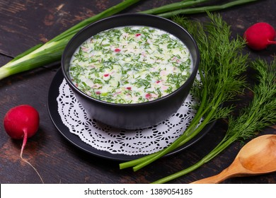 Russian summer cold soup okroshka from greens, vegetables, kvass and kefir on a black wooden table