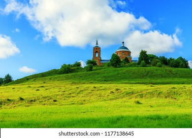 Russian summer with green hills with grass on the background of the old Russian Church.