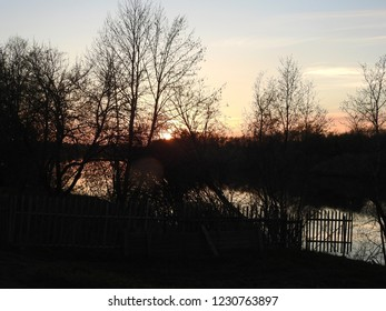 Russian sunset with view past silhouette trees to the River Luga