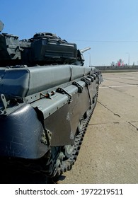 A Russian tank is standing on a concrete landing strip of a military airfield. On the body of the tank there are blocks of active protection.