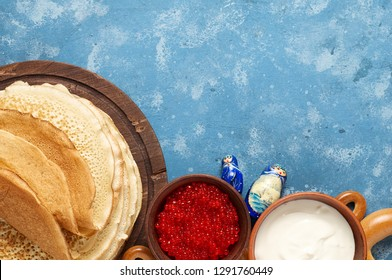 A Russian Tea Party including thin pancake blini, red caviar, sour cream and bagels. Shrovetide Maslenitsa festival meal on blue background. Overhead view with copy space