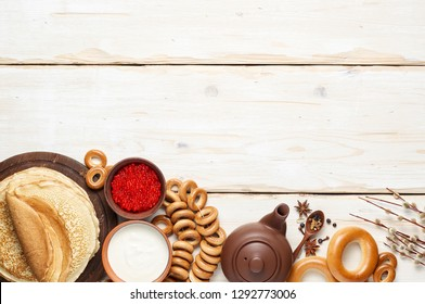 A Russian Tea Party including thin pancake blini, red caviar, sour cream and bagels. Shrovetide Maslenitsa festival meal on white wooden background. Overhead view with copy space