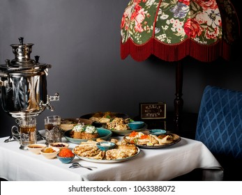 Russian tea traditions. beautiful russian pancakes (blini) with different toppings on the table:  caviar, honey, sourcream, jams. Samovar. Russian cuisine, vertical photo