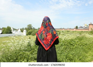 Russian tourist woman in traditional national Pavlovo Posad folk shawl, Pavloposadsky scarf. Kremlin in Suzdal town, Vladimir region, Russia. Travel, tourism in Russia. Russian style. Suzdal landmark