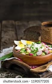 Russian traditional cold soup okroshka with potato, ham, cucmebers, eggs, radish, spring onion and kvass. Copyspace background.