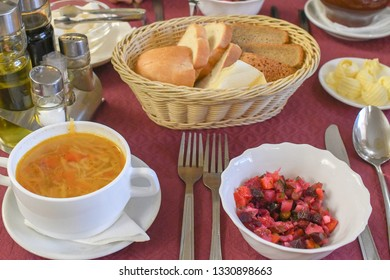 Russian traditional meal cabbage soup - Shchi  , Beet root salads - Vinegret or vinaigrette , with bread and butter in russian restaurant