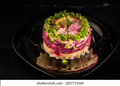 Russian traditional salad, dressed herring under fur coat on black plate on black background. Russian national cuisine.