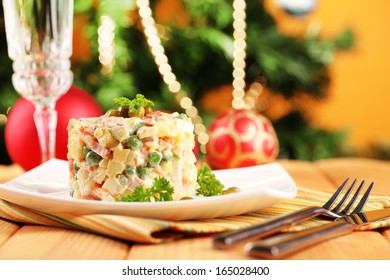 russian traditional salad olivier on color napkin on wooden table on bright background