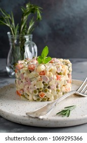 Russian traditional salad Olivier with vegetables and meat. Salad on a plate on a gray stone background