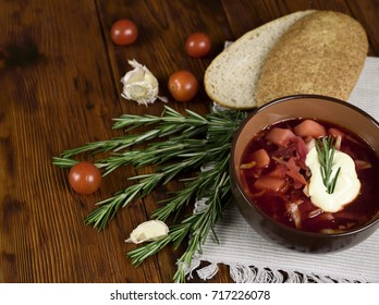 Russian traditional soup - with grain bread, cherry tomatoes. On a dark wooden table