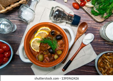 Russian traditional soup solyanka with meat and sausages, olives, tomatoes, lemons and mushrooms in a white bowl on a wooden table
