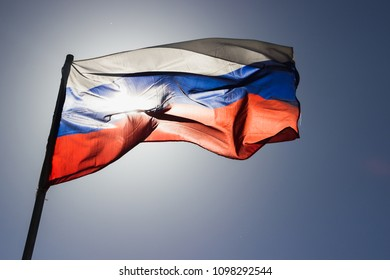 russian tricolor flag flying in slow motion and back lit by the sun.