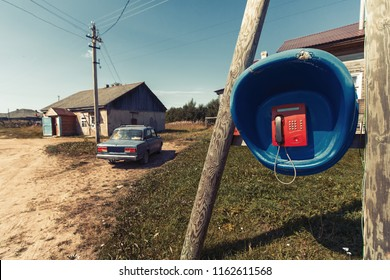 Russian village, landline, wooden houses and old car.
